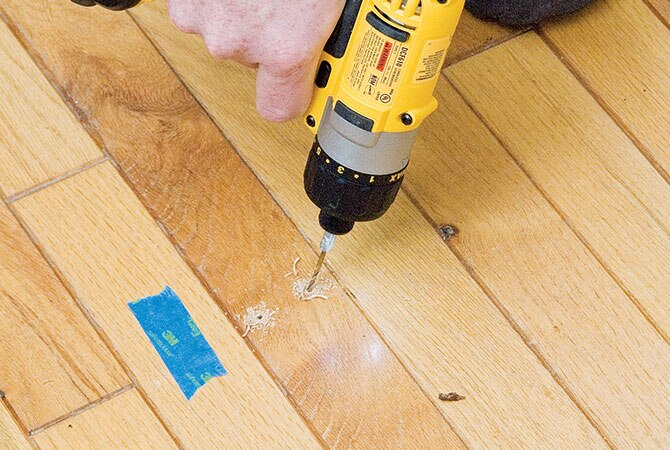 Drill angled pilot holes for the nails. Choose a bit that makes it easy to  nail but still grips the nail—a 3⁄32-in. bit should be about right. - How To Fix A Squeaky Hardwood Floor STANLEY Tools